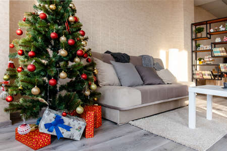 interior of a bright cozy room with a sofa and a Christmas decorated tree