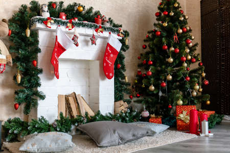 decorated white fireplace with socks and Christmas tree with gifts Stock fotó - 134721078
