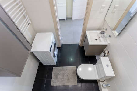 top view of a bright bathroom with a washing machine, washbasin and toilet