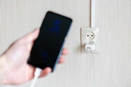 blurred smartphone on a charge in hand on a background of a wall outlet