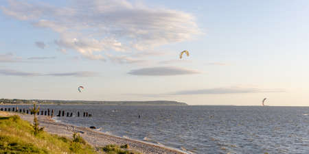 kitesurfers ride the sea on a sunny evening against the backdrop of a beautiful landscape 免版税图像