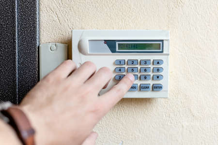male hand turns on the alarm in the apartment