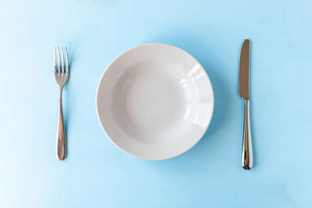 empty plate, knife and fork on light blue background 免版税图像