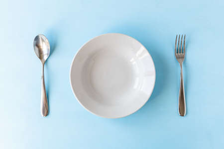 empty plate, spoon and fork on light blue background