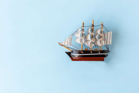 model of a wooden sailing boat on a light blue background, copy space