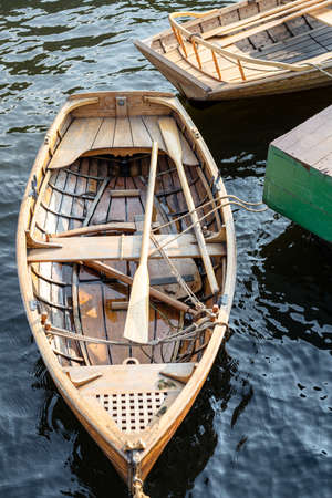 wooden boat with oars at the pier