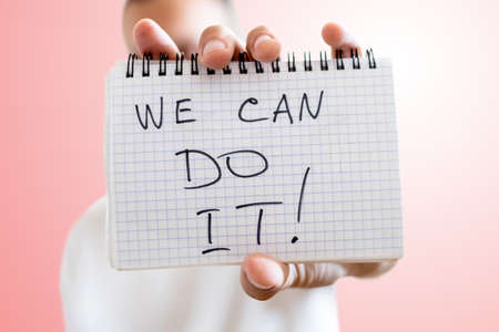 sheet of paper with the inscription WE CAN DO IT in hand on light red background