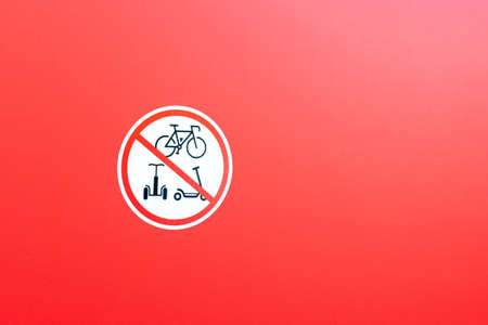 sign prohibiting bicycles and scooters on a red wall, copy space