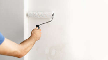 hand paints the wall with white paint with a roller, copy space