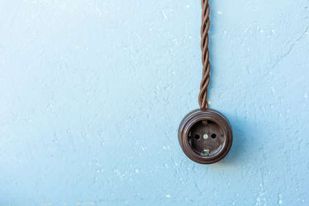 old brown european socket on blue wall, copy space