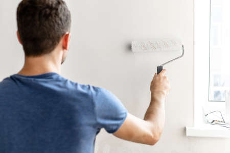 a man paints the wall with a roller white