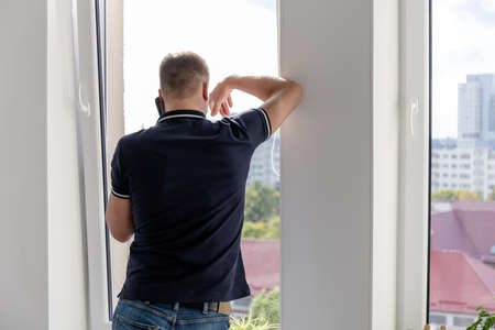 a man talking on the phone standing by a large window, view from the back