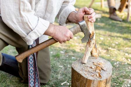 a man chopping a branch with an ax