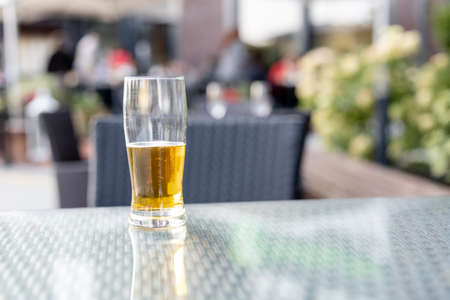 a glass of beer on a table in a street restaurant