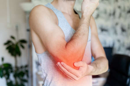 a man holds his elbow in pain against the background of the room