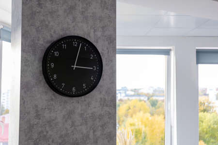 big black clock on the wall in a bright room