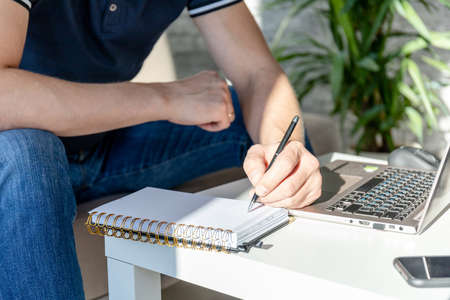 a left-handed man works at home at a laptop while sitting on the couch with a notebook and a pen in his hands 免版税图像