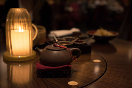 Candle, teapot and Chineese food in plates in Chineese restaurant Stock Photo