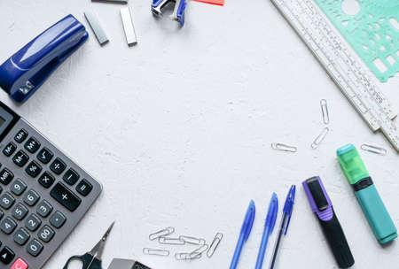 Office supplies are placed on a white background with an empty area in the center.Markers, pencils, pens, calculator, bookmarks, paper clips, stapler.