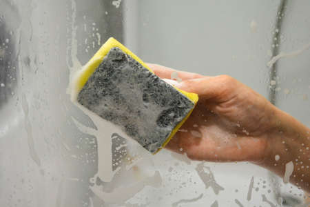 A womans hand with a yellow sponge washes the glass in the shower stall