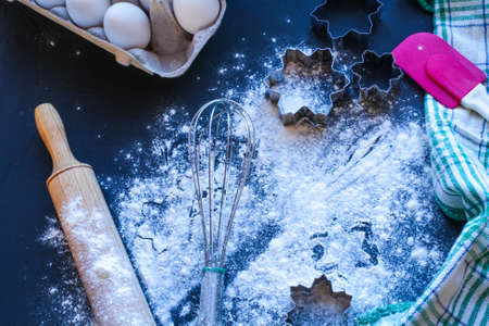 Baking utensils and ingredients are spread out on the dark surface.