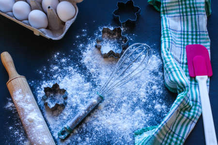Baking utensils and ingredients are spread out on the dark surface. Banque d'images
