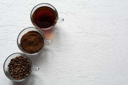 Three clear glass cups with ground coffee, coffee beans and brewed coffee in one row on a white background