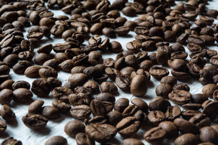 Roasted coffee beans scattered on a white surface
