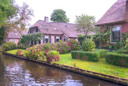Giethoorn, village of Holland with canals and rural houses on a cloudy day