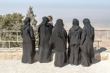MOUNT NEBO, JORDAN-FEBRUARY 2015. Arab women with black veil contemplating the landscape of MOnte Nebo in Jordan on a sunny day.