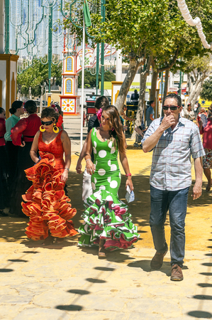 SEVILLA, ANDALUSIA, SPAIN-JULY 2015. Anonymous people dressed in flamenco at the Seville fair in Spain on a sunny day Foto de archivo - 115572739