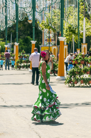 SEVILLA, ANDALUSIA, SPAIN-JULY 2015. Anonymous people dressed in flamenco at the Seville fair in Spain on a sunny day Foto de archivo - 115510756