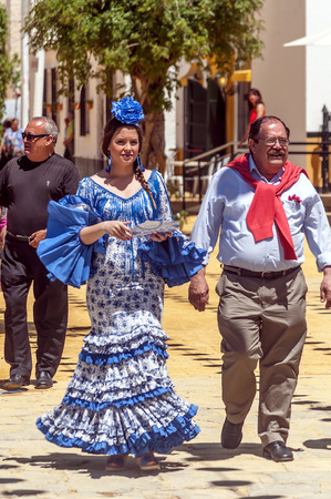 SEVILLA, ANDALUSIA, SPAIN-JULY 2015. Anonymous people dressed in flamenco at the Seville fair in Spain on a sunny day Foto de archivo - 115510761