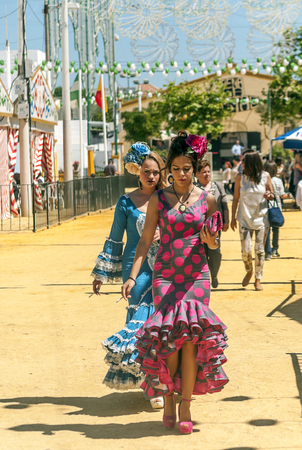SEVILLA, ANDALUSIA, SPAIN-JULY 2015. Anonymous people dressed in flamenco at the Seville fair in Spain on a sunny day Foto de archivo - 115572743