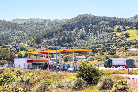 DEVA, BASQUE COUNTRY, SPAIN-JULY 2015. Truck refueling at a gas station surrounded by forest trees.