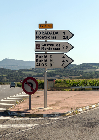 Road with distances in kilometers to different cities in Catalonia, Spain on a sunny day.