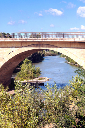 Ancient bridge over a river in France on a sunny day. 免版税图像