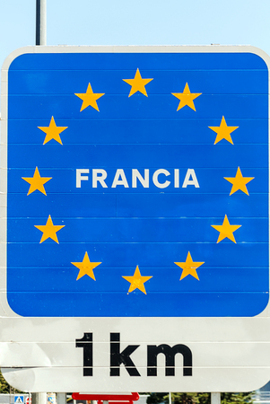 Poster indicating one kilometer distance between Spain and France on the border in Catalonia