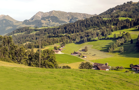 Mountains of the Swiss Alps with wooden huts and meadows on a sunny day. Banque d'images