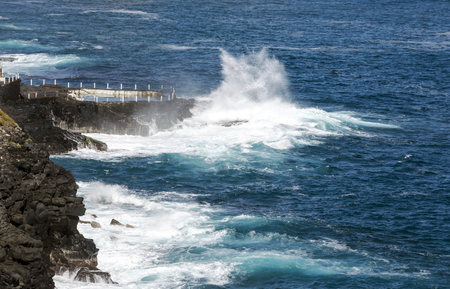 Waves breaking along the rocks in Tenerife, in the Canary Islands on a sunny day. Stockfoto