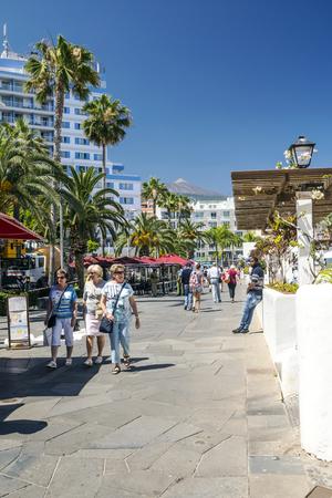 PUERTO DE LA CRUZ, CANARY ISLAND,  SPAIN - JUNE 2016. Anonymous tourists walking through a palm tree promenade in Puerto de la Cruz on a sunny day. It´s a touristic village near the sea.
