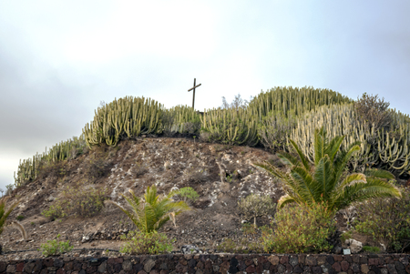 Cross in the gardens of a mountains on a cloudy day.