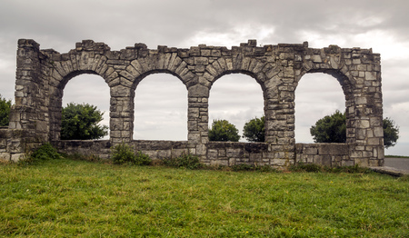 Grasslands in the Basque country with a ancient monument on a cloudy day Archivio Fotografico