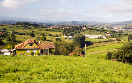 Rural town in the meadows near the mountains in Asturias in the north of Spain in a sunny day 写真素材
