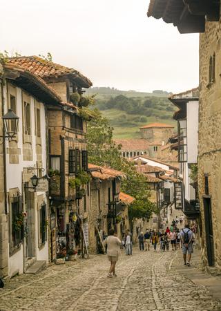 Santillana del Mar, Hiszpania wrzesień 2018 r. Ludzie chodzą na ulicy średniowiecznej wioski w pochmurny dzień.