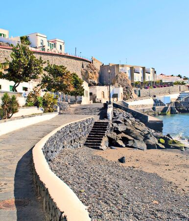 Road on the beach with white houses on one side in the south of the canary island of Tenerife in a sunny day