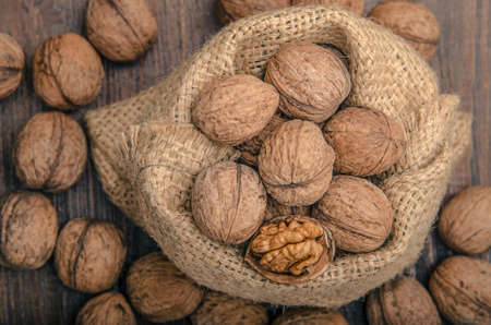 un healthy: Pile of walnuts in shellin a bag on a wooden background . Linen sack with walnuts in the background. toning
