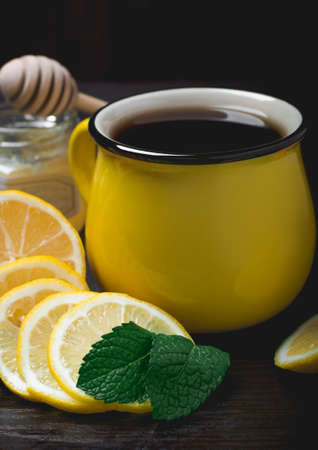 curative: Hot lemon tea with honey and mint on a wooden table