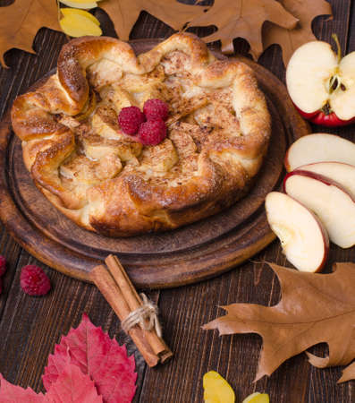 apple pie with cinnamon and raspberry on a wooden background Stock Photo