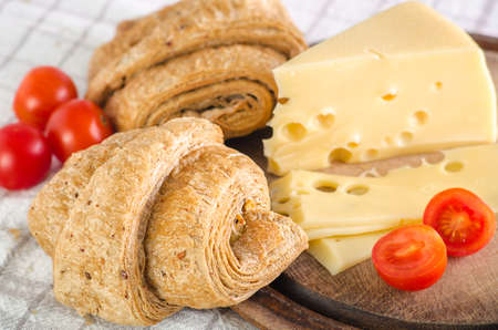 Morning breakfast with croissant, cheese and tomatoes. Stock Photo